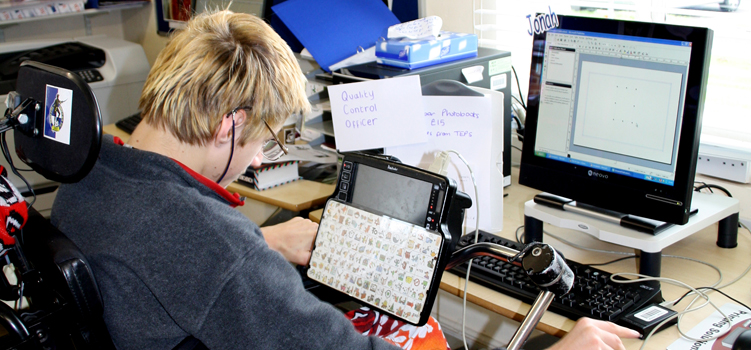 Student using an AAC device and interacting with a computer