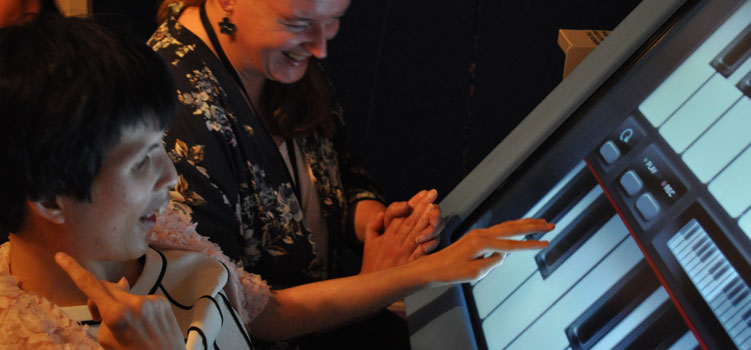 Lady enjoying a music session using a touch screen piano