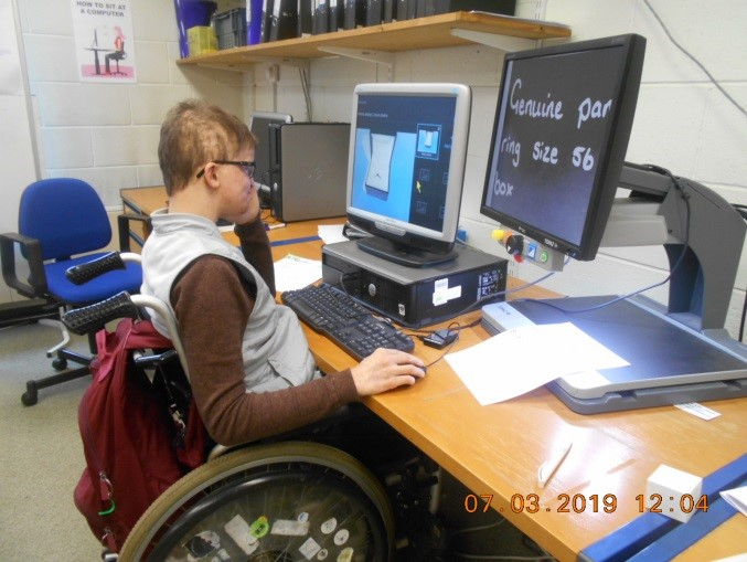 Jacob (Kuba) sitting in his wheelchair working at a computer