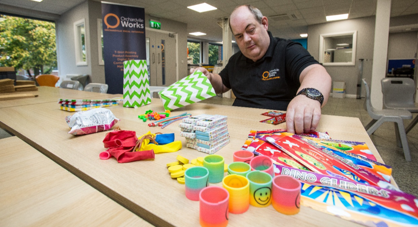 Orchardville worker creating party bags