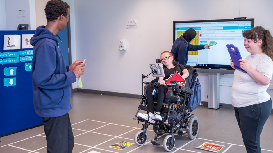 Four students having fun learning to code, one interacting with a touch screen, the other on an iPad, and two others mapping items on a grid on the floor