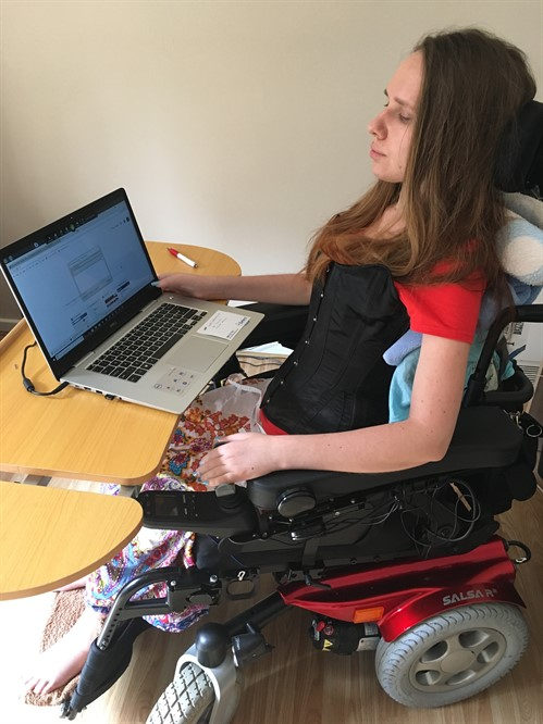 Dorota, a lady in an electric wheelchair sitting in front of a laptop computer