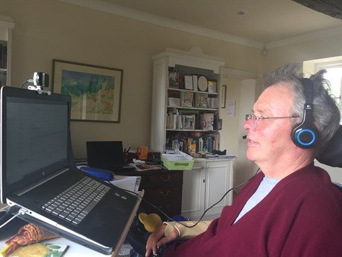George, wearing a headset, sitting in front of a laptop computer and dictating to the computer.