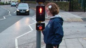 Young lady waiting at a traffic light pedestrian crossing