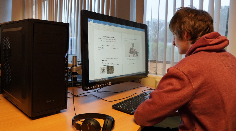Student sitting in front of newly upgraded computer