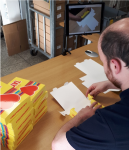 Darren using the video learning technique to assemble a packaging box for Tayto.