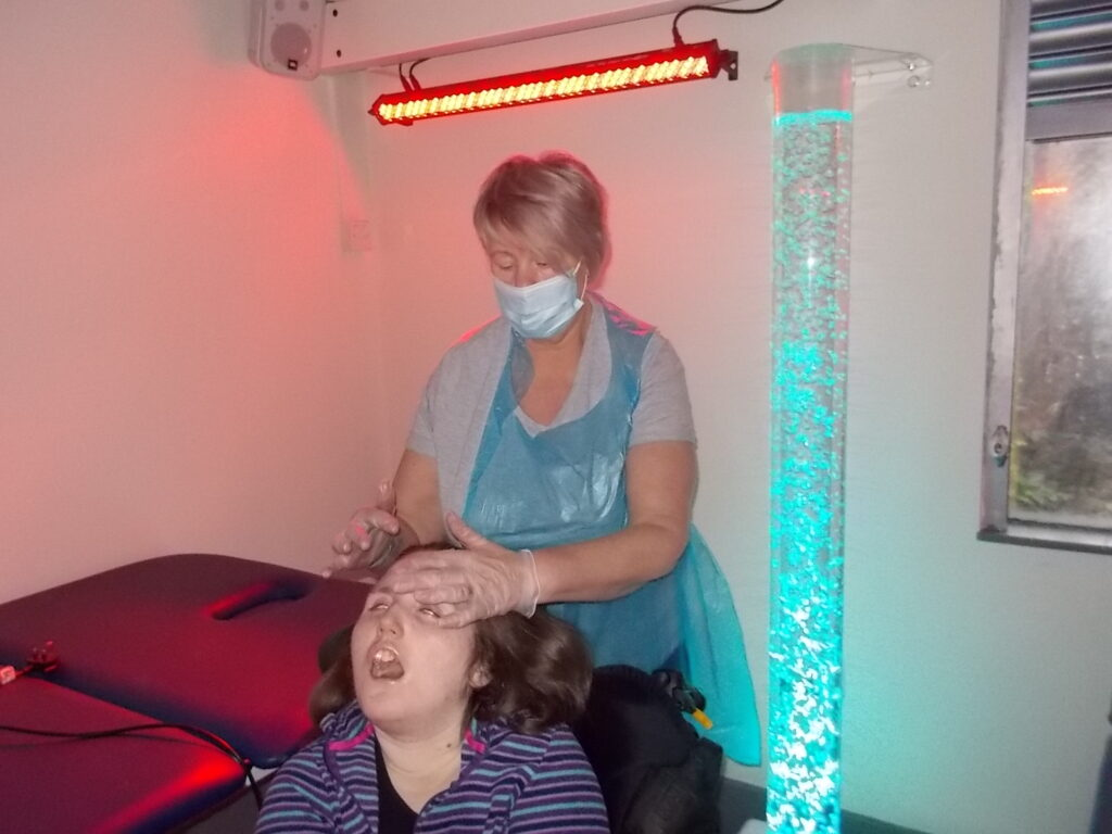 Photo of Ellie with a support worker in the sensory room