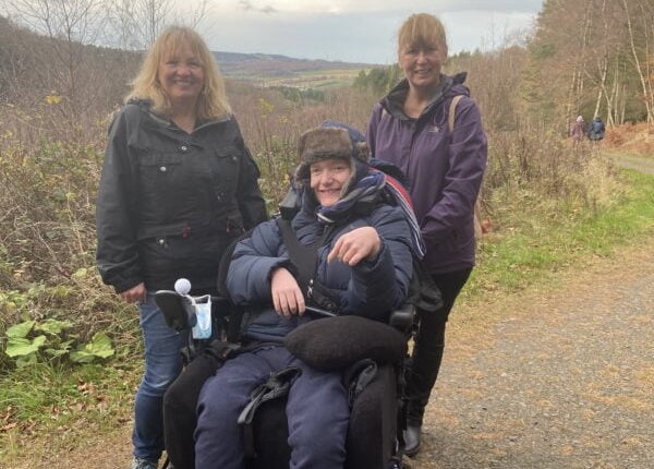 Nicholas Cornwell sitting in a wheelchair with two ladies either side of him