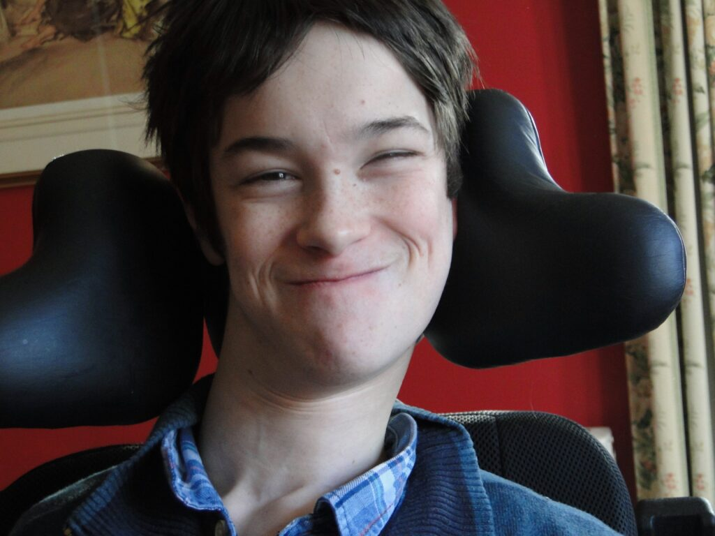 Oscar sitting in his wheelchair and smiling