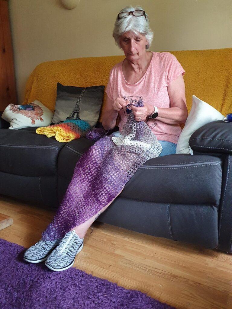 a lady sitting on a sofa Crocheting