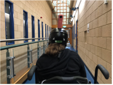 Student in wheelchair filming around College with a 360 camera mounted on a bike helmet