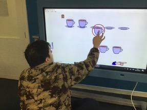 Charlie pairing the cups to the saucers using a big interactive screen