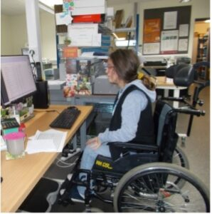 Amelia, in a wheelchair sitting in front of a computer while undertakening a work experience placement